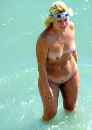 Абсолютно обнаженная женщина на пляже - фото 11
