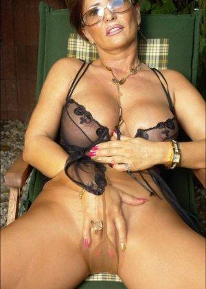Длинноногая женщина в чулках позирует в саду - фото 8