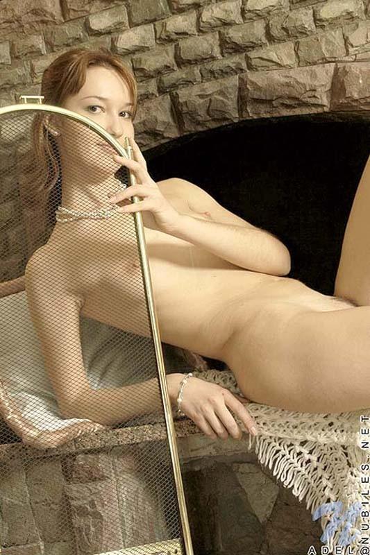 Пикантное позирование молодой девушки у камина