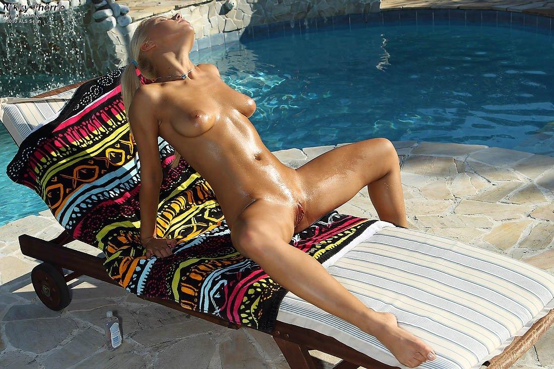 Яркая блондинка загорала у бассейна в бикини