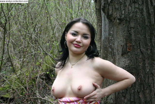 Пухлая русская брюнетка эротично позирует в лесу
